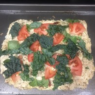 Take out of the oven and add sliced tom, kale, basil,
